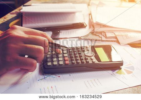 Close up man using calculator and doing finance in home office.