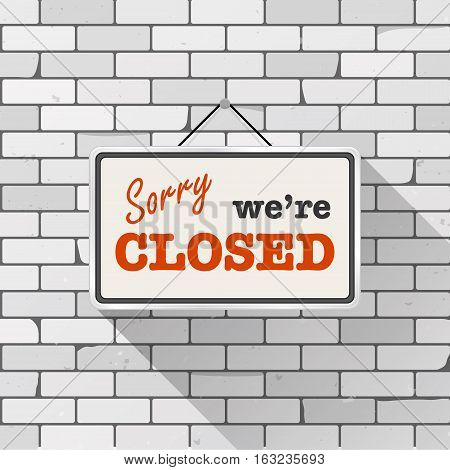 Simple white sign with text 'Sorry we're closed' hanging on a gray brick wall. Grunge brickwork background textured rough surface. Creative business interior template for shop store supermarket.