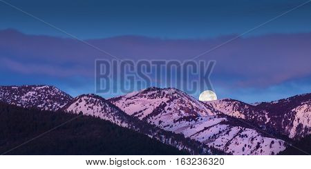 Moon rise over mountains with alpen glow pink light