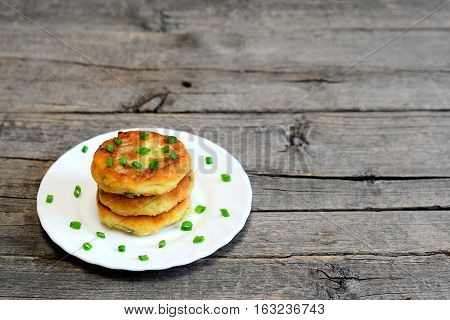 Mixed vegetable cutlets on a plate isolated on wooden background with copy space. Fried cutlets made of potatoes, green peas, carrot and green beans and garnished with fresh green onion. Veggie recipe