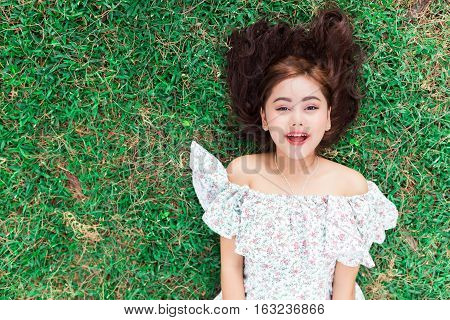 Smiling Happy Woman Lying Down On A Grass.
