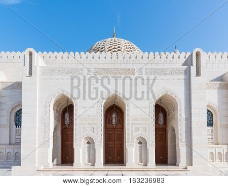 Exterior detail with entrance doors and the dome in the background of the Sultan Qaboos Grand Mosque in Muscat the main mosque of The Sultanate of Oman.