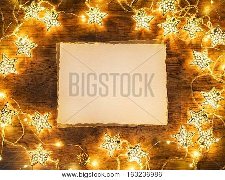 Old paper with garland on wooden background. Top View. Merry Christmas and Happy New Year!!
