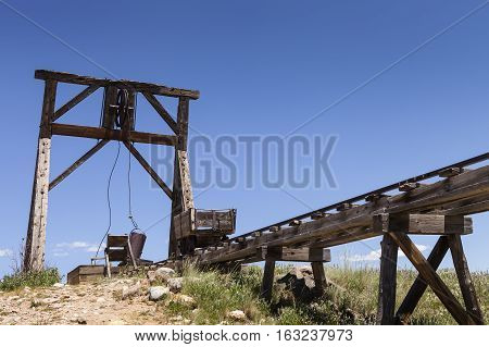 Old mining ore cart on trestle with head frame under blue sky.