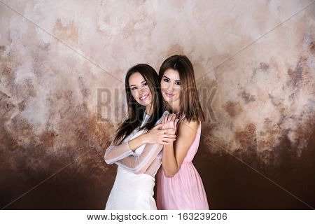 Two adult  look alike brunette sisters smiling holdind each otherand looking on camera