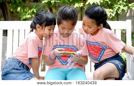 Bangkok, Thailand - August 15, 2016 : Three cute little sisters playing outdoor mobile game on their smart phones. Young Asian girls Kids using internet sitting on a white bench in garden.
