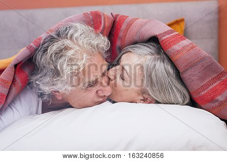 Adult Couple Kissing In Bed Before Sleeping