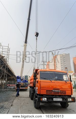 Tyumen, Russia - July 31, 2013: JSC Mostostroy-11. Bridge construction for outcome of Melnikayte street and Shirotnaya streei in Tyumen. Mobile carane unloads equipment from truck