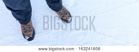 Low section of woman standing with winter boots in the snow