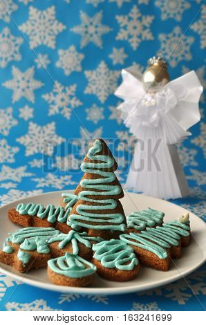 Decorated Christmas honey cookie on blue winter background with snow flakes and an angel