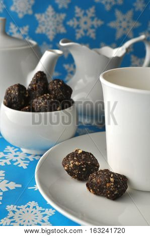 Tea set with raw walnut, date and cacao balls on a blue winter background with snow flakes