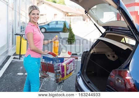 Woman After Shopping Loading Grocery In Car