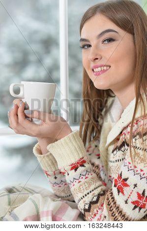 Beautiful girl in warm sweater drinking tea near the window