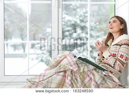 Woman reading book and drinking tea sitting on windowsill