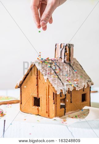 Man sprinkles Homemade gingerbread house confectionery sprinkling on white background