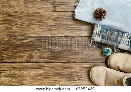 winter knitted clothes . Cashmere sweater ugg boots and wool square scarf on wooden background. Concept for Winter and Christmas. Copy space.