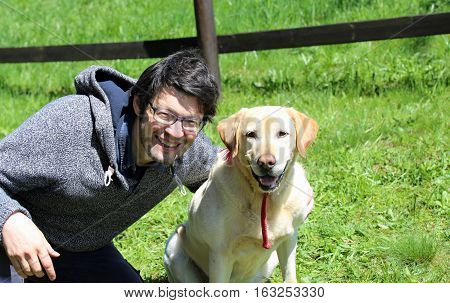 man with blacks hair smiling with his labrador dog