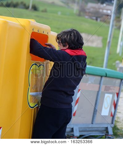 Poor Boy Looks Into The Yellow Garbage Can In Search Of Somethin