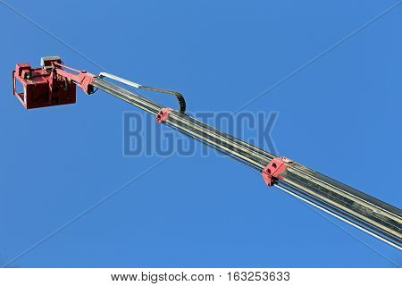 metal basket of an aerial platform with mechanical arm extended to maximum