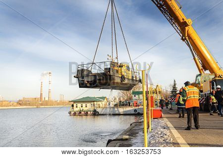 MOSCOW, RUSSIA - NOVEMBER 11, 2016: State Unitary Enterprise Mosvodostok performs recovery vessels on coastal winter parking. River vessel carries a crane.