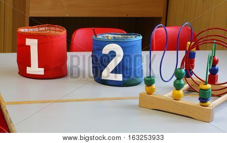 Two Jars With The Written One And Two In The School Bench