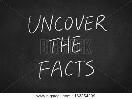 uncover the facts concept word on blackboard background