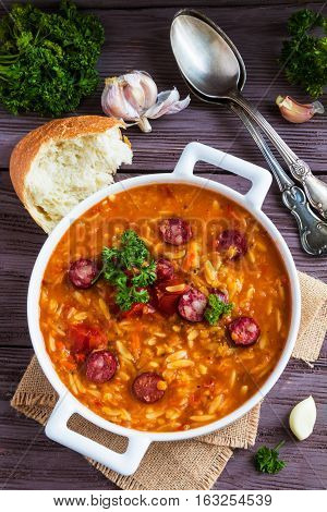 Tomato soup with orzo and smoked sausages in white casserole on wooden rustic table. Fresh bread and parsley vintage spoon top view.