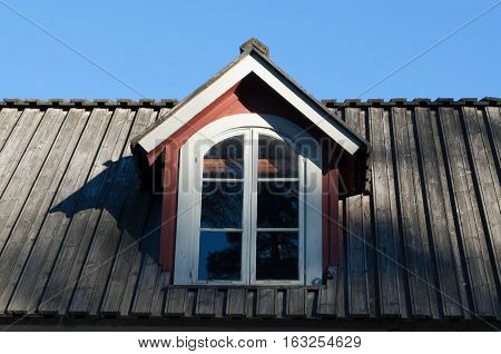 Dormer window on old wooden house roof.