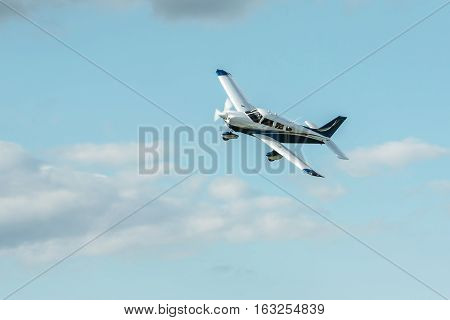 Single piston aircraft. Single-propeller aircraft flying over the blue sky at a small airport