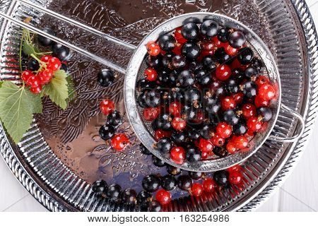 Red and black currants in metal sieve. Top view.