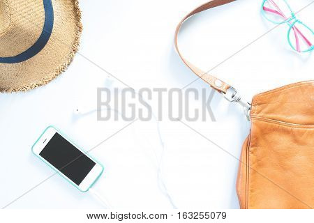 Flat lay female accessories collage with hat bag fashion glasses mobile phone and earphone on white background.