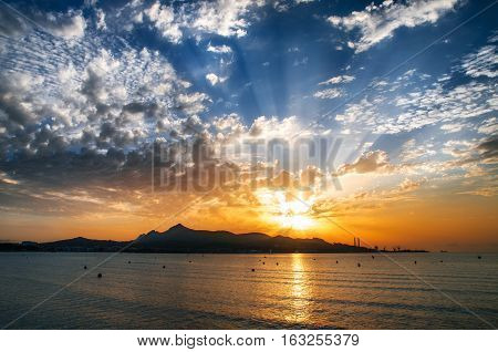 Majorca Puerto de Alcudia beach pier at sunrise in Alcudia bay in Mallorca Balearic islands of Spain. Sun rises over the mountains in the sea