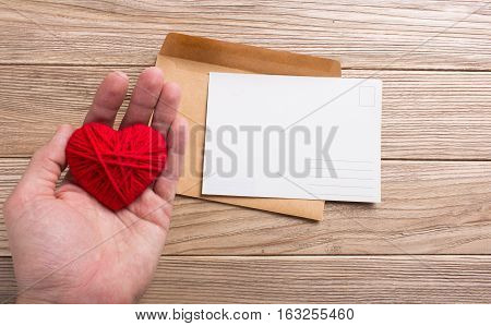 Empty postcard in hand with heart. On the wooden table. postcrossing