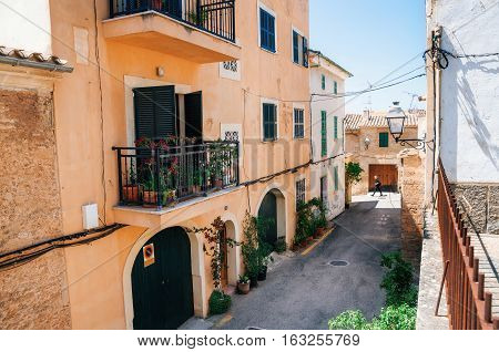 Alcudia Mallorca Spain - May 23 2015: Adult walks through the narrow streets of historical town part of Alcudia with its traditional house and architecture