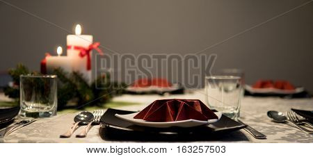 detail of untouched table setting before elegant dinner during holidays with candle light