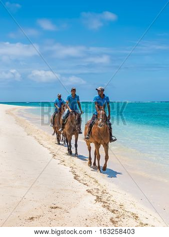 Le Morne Mauritius - December 7 2015: Men ride horses on the Le Morne Beach one of the finest beaches in Mauritius and the site of many tourism facilities.