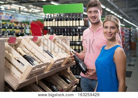 Beautiful Young Couple Shopping Vino In Supermarket