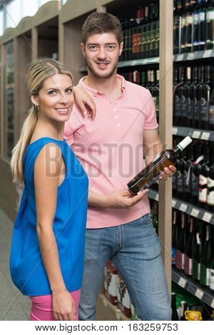 Smiling Couple Buying Vino In Supermarket