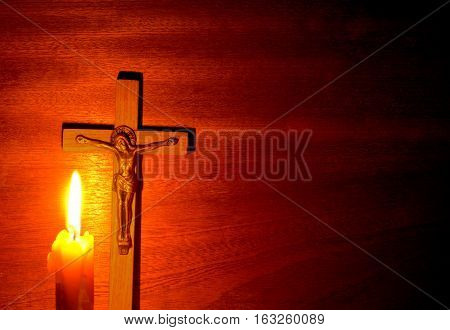 Fire of candle and crucifix in the dark on wood background