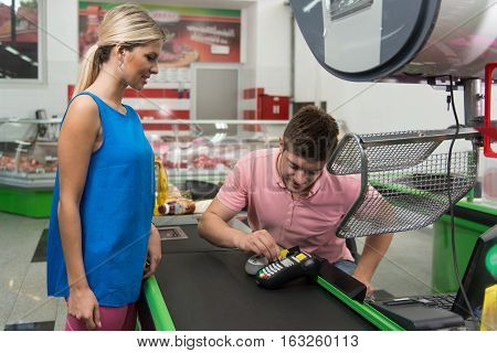 Woman Paying For Shopping At Checkout With Card