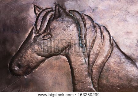 inlaid horse in copper as a background