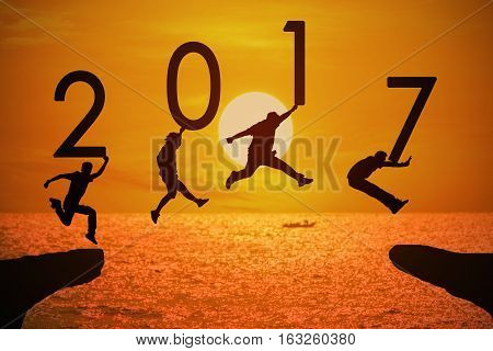 Silhouette group of young mans jumping and holding numbers 2017 over a beautiful sunset at the sea, background for happy news years.