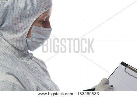 woman in a protective suit is writing on paper