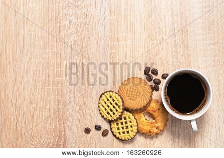 Cup of hot coffee and various cookies on wooden table top view. Space for text