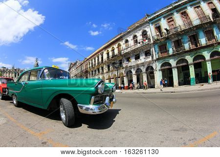 Classic old American car in front of El Capitolio. Classic cars are still in use in Cuba and old timers have become an iconic view and a worldwide known attraction.