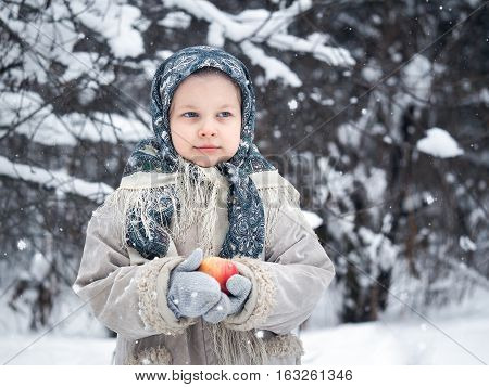 The little girl in the woods in winter with a red Apple on hand