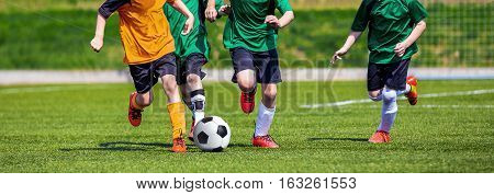 Running Youth Football Players. Kids Playing Football Soccer Game on Sports Field. Boys Play Soccer Match on Green Grass. Youth Soccer Tournament Teams Competition.