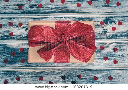 Love holiday concept. Gift with red ribbon and hearts on a wooden board.