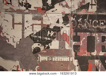 Background of an urban wall with lots of pieces of old glued posters