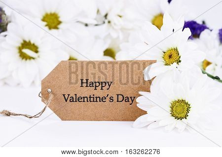 Valentines Day card and daisies. Extreme shallow depth of field with selective focus on card.